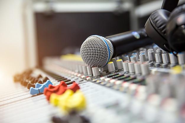 Close-up, o microfone é colocado no mixer de áudio profissional no estúdio para viver o conceito de produção de mídia e equipamento de som.