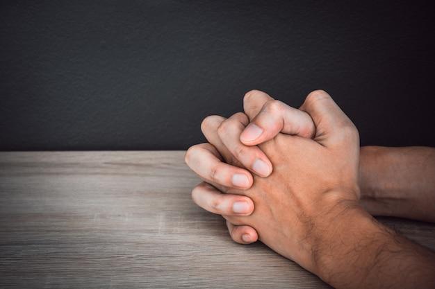 Close-up orando com as mãos na mesa de madeira com fundo de cor preta na parede