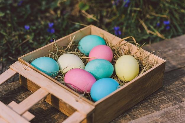 Close-up, ovos em uma caixa de madeira em um fundo de flores. conceito de páscoa.