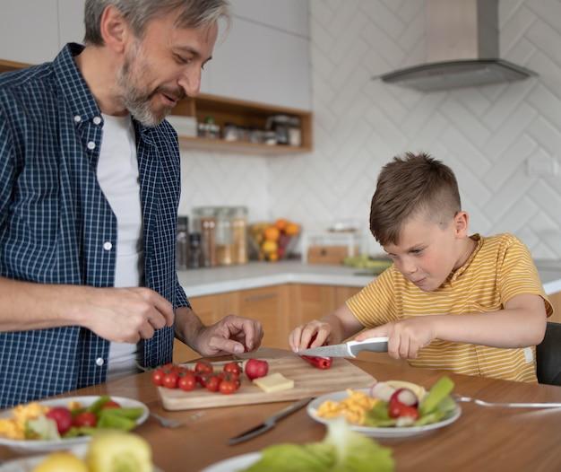 Close-up pai e filho cozinhando