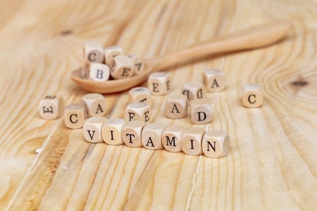 Close-up palavra vitamina feita a partir de letras de madeira sobre a mesa e abcde na colher de madeira