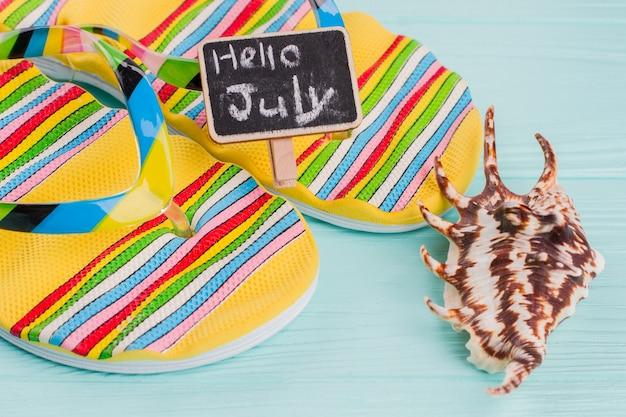 Close-up par de chinelos brilhantes e concha do mar sobre o fundo azul. olá julho escrito a giz.