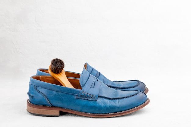 Close-up par de novos sapatos de couro elegantes e luxuosos mocassins, escova de madeira para sapatos, horizontal, espaço de cópia