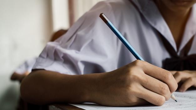 Close-up para exame com estudante de escola uniforme fazendo teste educacional com estresse em sala de aula.