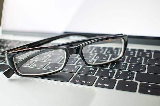 Close-up para os óculos de empresários em computadores portáteis.