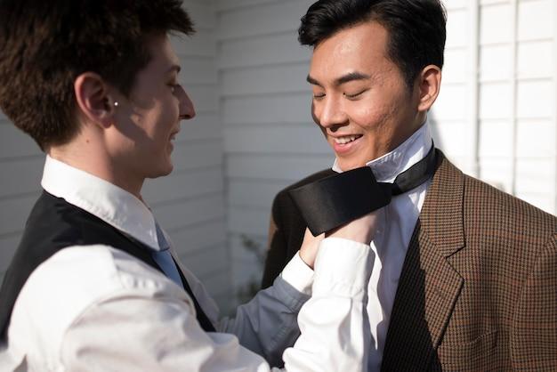 Close-up parceiro arranjando gravata