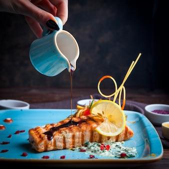 Close-up peixe grelhado, mão derramando molho com guarnição, limão, molho e especiarias num prato azul sobre uma mesa de madeira escura