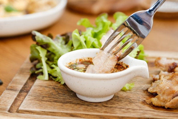 Close up pescoço de porco cozido no carvão com o molho é picante sour taste é um aperitivo popular na tailândia.