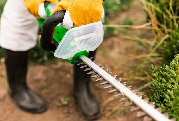 Close-up, pessoa, usando, aparando ferramenta, ligado, bush