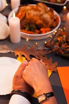 Close-up pessoas de mãos dadas no jantar