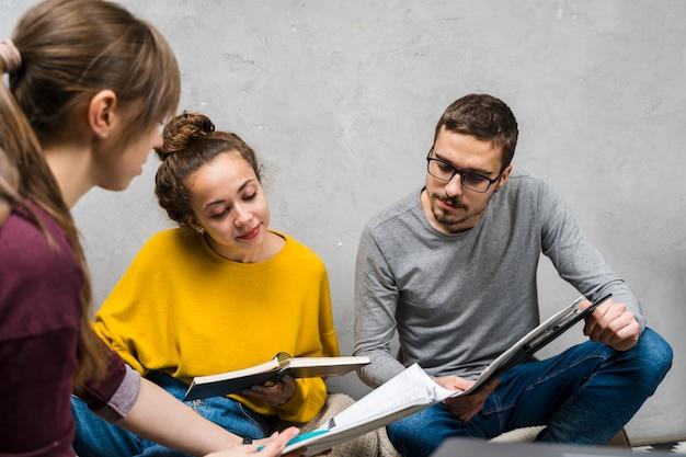Close-up pessoas estudando juntos dentro de casa