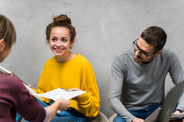 Close-up pessoas sorridente estudando juntos dentro de casa