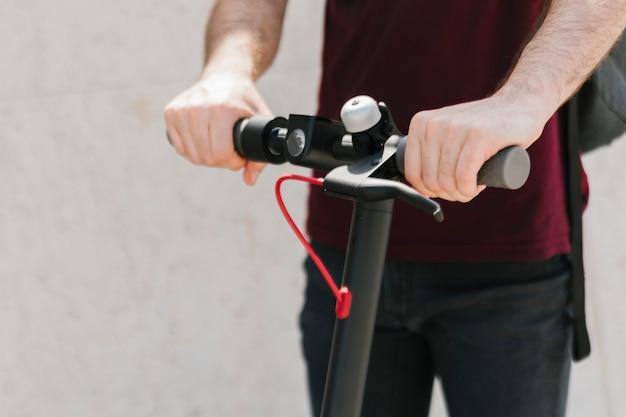 Close-up piloto e-scooter com fundo desfocado