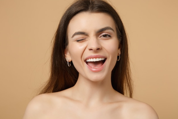 Close-up piscando morena mulher seminua sorridente de 20 anos com a pele perfeita isolada no retrato de parede bege pastel. conceito de procedimentos cosméticos de saúde de cuidados com a pele.