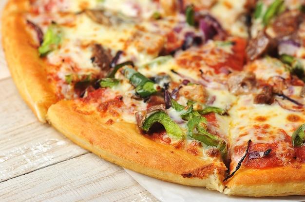 Close-up pizza redonda cortada em pedaços em um fundo de madeira