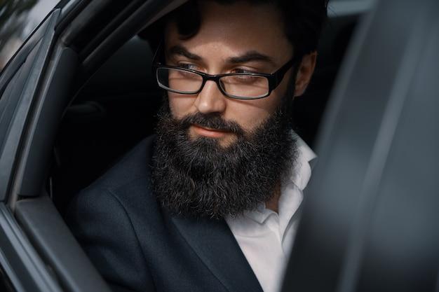 Close-up portrair atraente jovem empresário em um carro