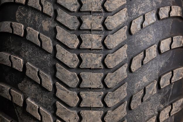 Close-up pretos novos pneus dirigindo um carro