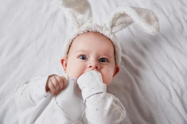 Close up.pretty bebê em uma roupa de coelho, deitado na cama. conceito de férias