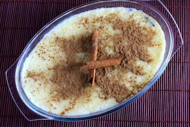 Close-up pudim de arroz com canela na tigela de vidro na toalha de mesa de bambu