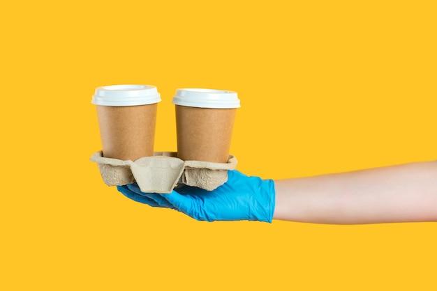 Close-up recortado entregador de luva azul segurando duas xícaras de café para viagem