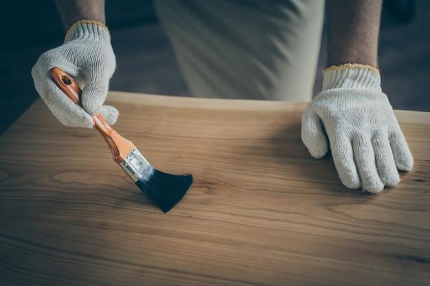 Close up recortado profissional qualificado cobrindo mesa de laje feita à mão pincel de tinta verniz à prova d'água negócios de madeira indústria de marcenaria loja interna