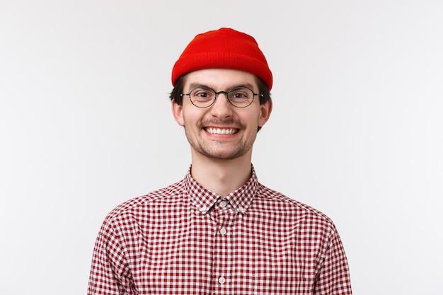 Close-up retrato alegre engraçado jovem com barba e bigode, sorrindo encantado dentes sorriso perfeito, usar óculos e gorro vermelho, otimista de pé, emoções positivas