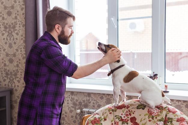 Close up retrato bonito jovem hippie homem joga e ama seu bom amigo cachorro em casa. emoções humanas positivas, expressão facial, sentimentos.