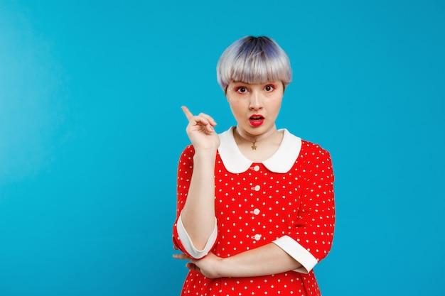 Close-up retrato chateada linda garota dollish com cabelo violeta leve curto, vestido vermelho sobre parede azul