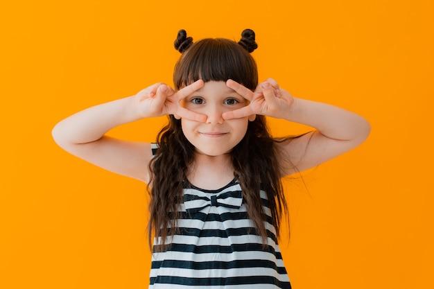 Close up retrato criança menina adorável alegre emoção facial expressando lindo sorriso muito jovem vestindo vestido listrado isolado parede amarela mostra dedos da vitória, crianças modernas