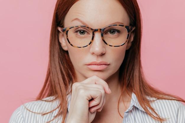 Close-up retrato de auto confiante empresário feminino detém o queixo, levanta a sobrancelha, usa óculos ópticos