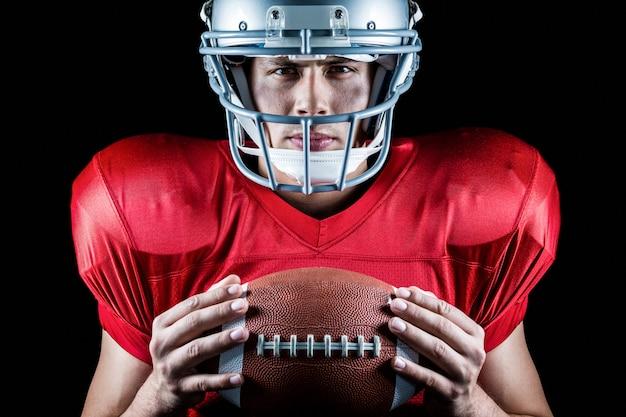 Close-up, retrato, de, confiante, jogador football americano, segurando bola