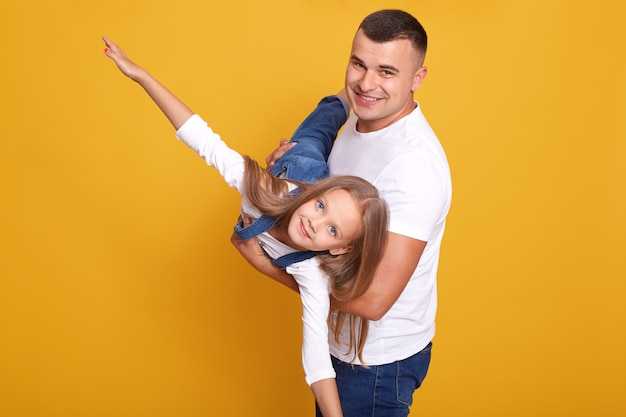 Close-up retrato de criança brincando com o pai dela, garota sendo nas mãos de pais, finge voar, espalha os braços para os lados