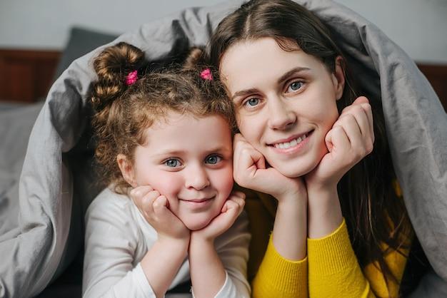 Close-up retrato de feliz criança pequena criança criança filha e alegre jovem mãe deitada na cama coberta com cobertor olhar para a câmera posando em casa, mãe de família e menina passar algum tempo juntos
