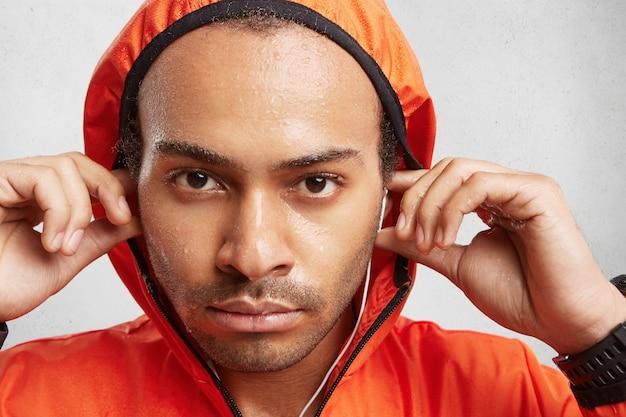 Close-up retrato de homem confiante de pele escura com cerdas, usando capuz de anoraque