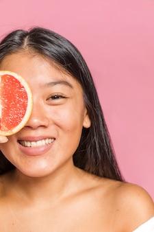Close-up, retrato, de, mulher sorri, e, um, toranja