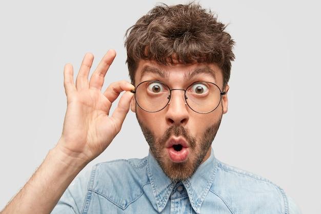 Close-up retrato de um homem bonito surpreso com a barba por fazer, olhando através dos óculos em perplexidade
