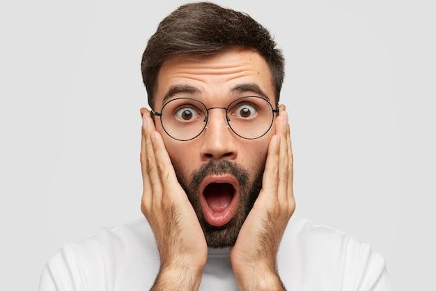 Close-up retrato de um homem jovem e bonito apavorado com a barba por fazer chocando-se no fundo de seu coração, tocando as bochechas com ambas as palmas, percebe algo inesperado, isolado sobre uma parede branca