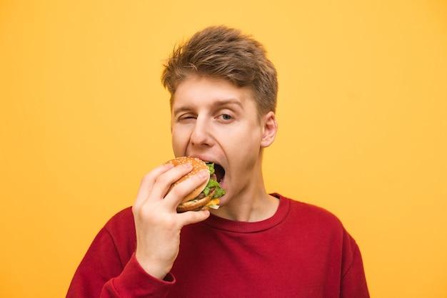 Close-up retrato de um menino comendo um hambúrguer em um amarelo