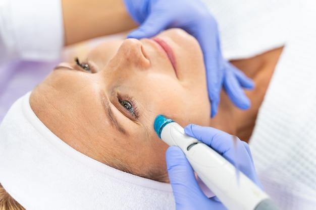 Close-up retrato de uma mulher adulta bonita e serena com uma bandana em tratamento de pele