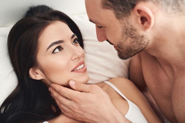 Close-up retrato de uma mulher de cabelos escuros muito contente olhando para o marido com amor infinito