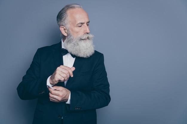 Close-up retrato dele ele agradável conteúdo atraente orgulhoso arrogante rico rico homem de cabelos grisalhos macho diretor executivo que fixa o botão olhando isolado sobre um fundo cinza escuro pastel