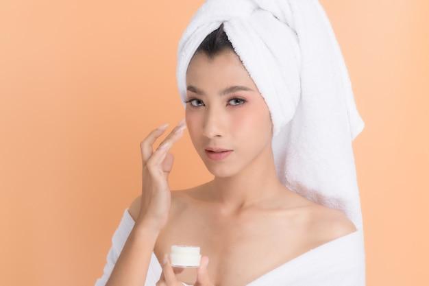 Close up, retrato lindo rosto de mulheres asiáticas em toalhas na cabeça aplicando creme de loção hidratante