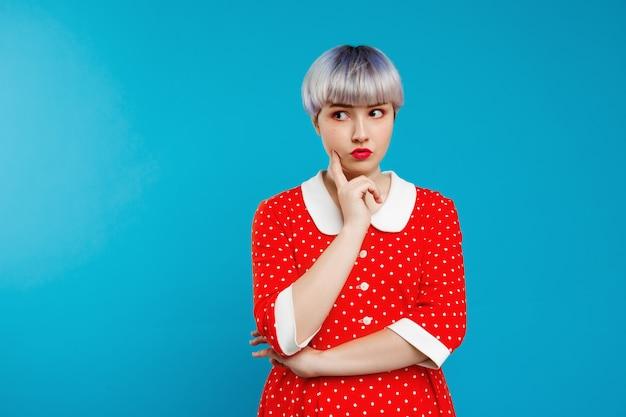 Close-up retrato menina bonitinha bonita com cabelo violeta leve curto vestido vermelho sobre parede azul