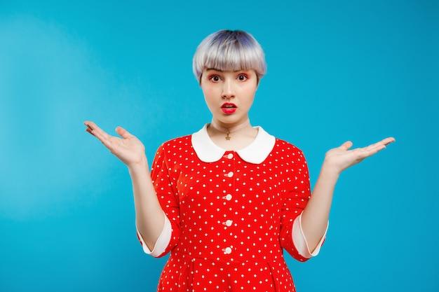 Close-up retrato querendo saber linda garota dollish com cabelo violeta curto luz vestido vermelho sobre parede azul