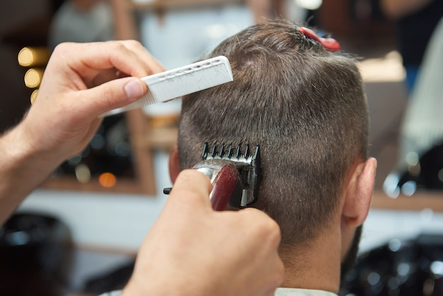 Close-up retrovisor de um homem recebendo um novo penteado de barbeiro profissional