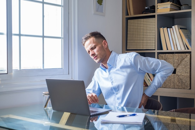 Close-up retrovisor estressado jovem tocando a parte inferior das costas sentindo desconforto, sofrendo de dor repentina devido ao estilo de vida sedentário ou excesso de trabalho do computador em postura incorreta no escritório em casa.