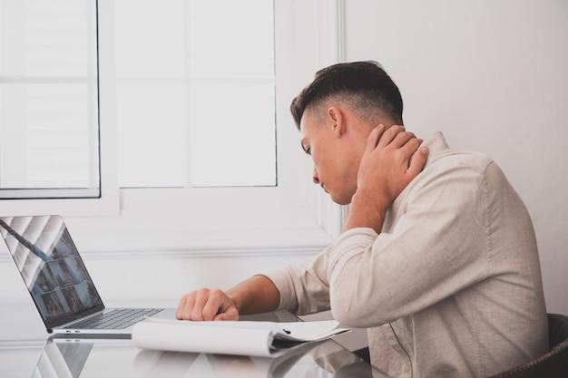 Close up retrovisor estressado jovem tocando a parte inferior do pescoço sentindo desconforto, sofrendo de dor repentina devido ao estilo de vida sedentário ou excesso de trabalho do computador em postura incorreta no escritório em casa.
