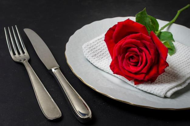 Close-up rosa vermelha em um prato com talheres