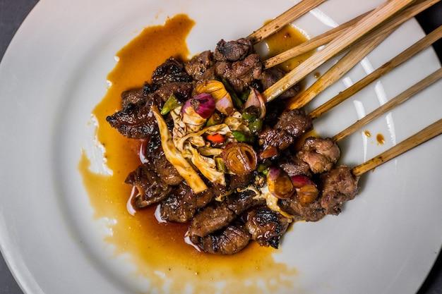 Close up satay prato de frango em um prato branco e um fundo preto