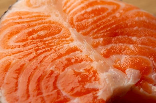Close-up sem a imagem de pessoas do pedaço de peixe vermelho cru parecendo fresco e molhado